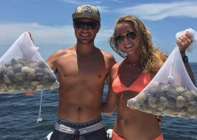 Couple holding huge nets of scallops caught from gulf of mexico. Fishing florida flats.